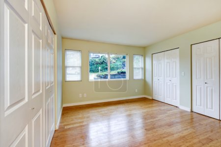 Photo for Empty room interior with hardwood floor and three closets with white sliding doors. Northwest, USA - Royalty Free Image