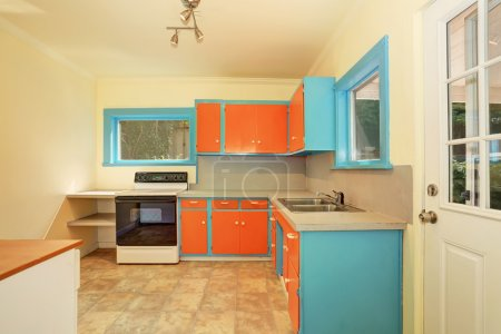 Old fashioned kitchen interior with orange and blue cabinets.