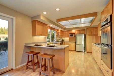 Bright wooden kitchen interior with steel appliances.