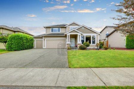 Photo pour Maison soignée beige avec deux places de garage et une grande allée en béton. Northwest, États-Unis - image libre de droit