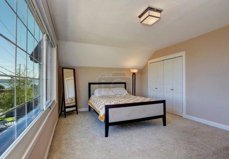 Photo pour Intérieur de chambre simple et élégant avec plafond voûté, beau lit avec literie jaune, placard de portes blanches et vue sur la fenêtre. Northwest, États-Unis - image libre de droit