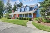American house exteriér s modrou a bílým lemem. Také červené dveře