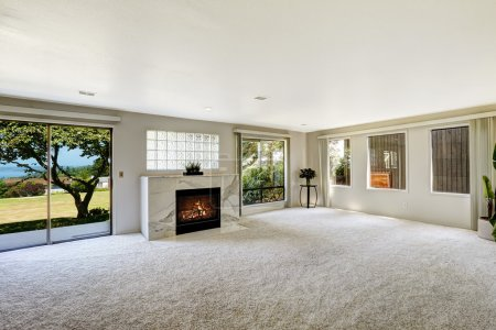 Photo for Bright empty room with fireplace and carpet floor. Glass slide door to backyard - Royalty Free Image