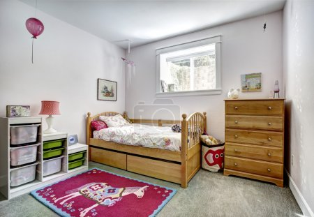 Photo for Cozy kids room with rustic bed and dresser. Cheerful red rug on carpet floor - Royalty Free Image