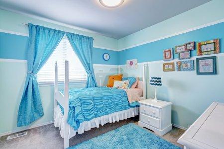 Photo pour Joyeux intérieur de la chambre des filles dans des tons bleu clair. Lit blanc avec poteaux hauts et literie bleue, tapis bleu et rideaux - image libre de droit