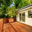 Wooden walkout deck with railings and decorated wi...
