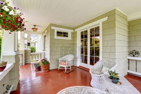 Photo pour Porche d'entrée dans une vieille maison avec chaises en osier et porte d'entrée en verre. Porche décorée avec des pots de fleurs - image libre de droit