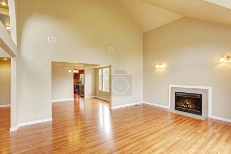 Empty living room with high ceiling and fireplace