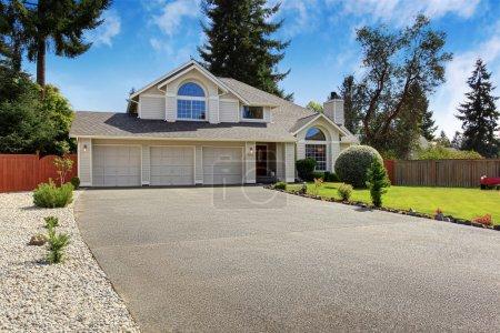 Photo pour Maison de luxe extérieure avec toit en tuiles. Maison avec garage à trois voitures et jardin avant paysage - image libre de droit