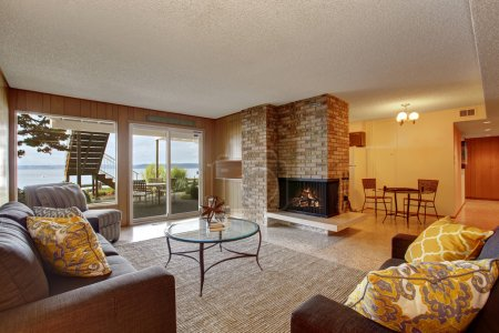 Basement living room with wooden wall trim, brick ...