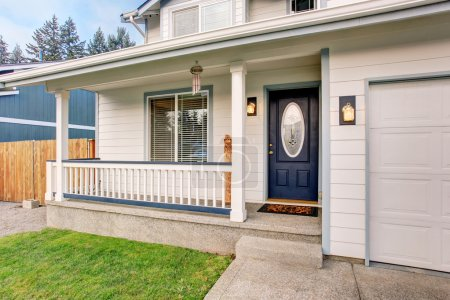 Traditional northwest home with navy blue door and white fencing