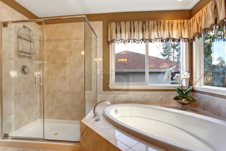 Large elegant master bathroom with tile floors, and glass shower
