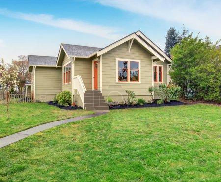 Photo pour Maison avec orange et blanc garniture beige, également herbe remplis de pelouse. - image libre de droit