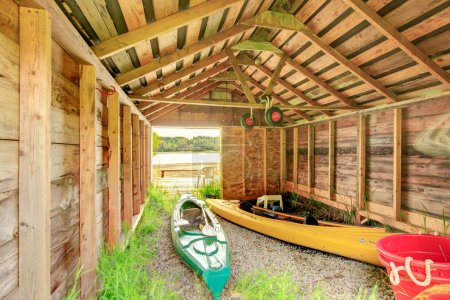Two kayaks sitting in an old wooden shed.