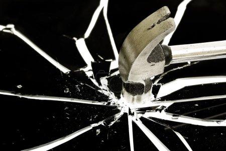 Photo pour Marteau brisant un verre noir - image libre de droit