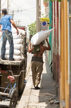 Photo for SANTA CLARA,CUBA-JULY 4,2014: Unloading a truck of flour in a Cuban dining room for people in need or social cases. One of the major achievements of the Cuban Revolution is serve those in need. - Royalty Free Image
