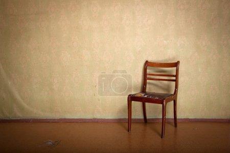 Photo pour Chaise déchiquetée antique dans l'intérieur de l'ancienne pièce avec papier peint vintage - image libre de droit