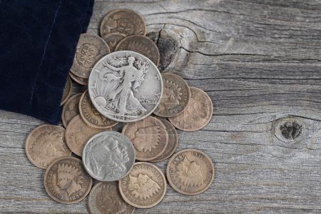 Photo for Close up view of a bag of United States vintage coins spilling out onto rustic wood - Royalty Free Image