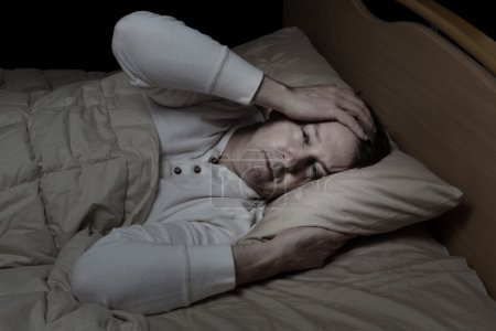 Photo for Horizontal image of sick mature man, holding his head, while in bed - Royalty Free Image