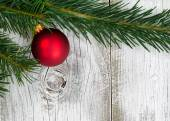 Grand fir branch with singe red ornament on rustic white wooden