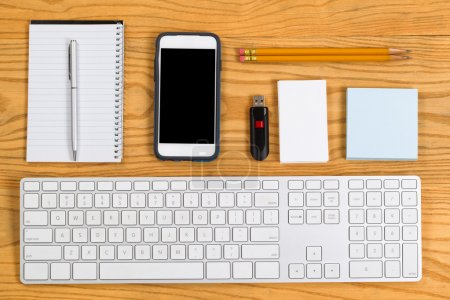 Photo for High angled view of a highly organized desktop consisting of computer keyboard, pencils, pen, cell phone, notepad, business cards and thumb drive. Horizontal layout. - Royalty Free Image
