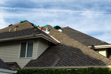 Photo pour Maison avec toit étant les nouveaux bardeaux remplacés montrant, papier-feutre et outils. Ciel bleu en arrière-plan. - image libre de droit