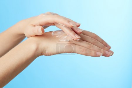Photo pour Mains féminines en crème hydratante sur fond bleu - image libre de droit