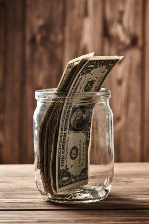 Saving. Dollars in glass jar
