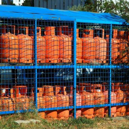 Photo pour Rangées de plusieurs conteneurs de gaz rouge à la station-service dans la rue - image libre de droit