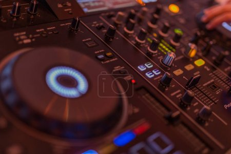 Photo for Dj mixes the track in the nightclub at party. Dj mixing outdoor at beach party festival with crowd of people in background - Summer nightlife view of disco club outside - Soft focus - Royalty Free Image