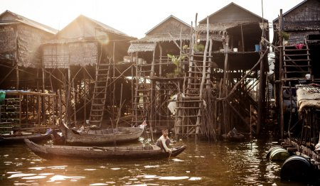 Unidentified people ride a boat in floating village