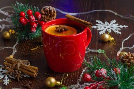 Photo pour Délicieux vin chaud chaud chaud avec cannelle, anis étoilé et orange en tasse rouge gros plan sur fond de Noël avec espace de copie. - image libre de droit