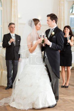 Bridal couple clinking glasses
