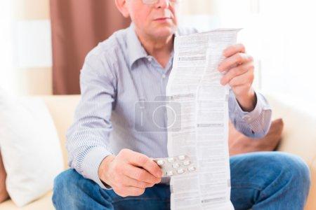 Photo pour Vieil homme affichant l'insert de paquet de medicament à la maison avec des glaces - image libre de droit
