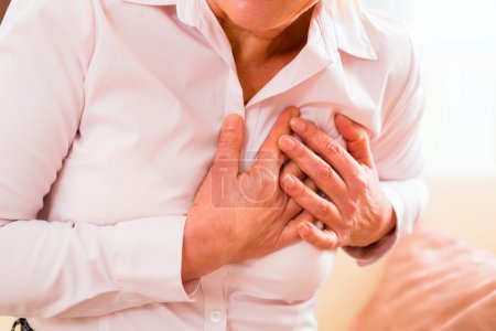 Old woman holding breast because of heart infarcti...