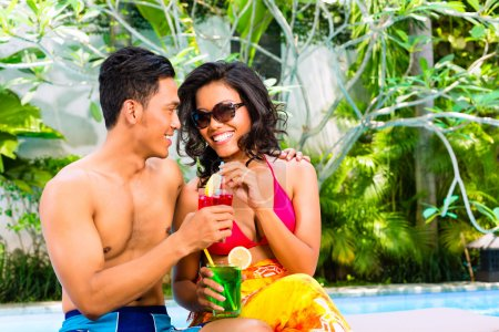Photo pour Couples asiatiques buvant des cocktails de fantaisie à l'hôtel ou à la piscine de club - image libre de droit