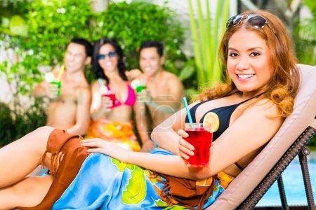 Photo pour Amis asiatiques faisant la fête et buvant des cocktails de fantaisie à l'hôtel ou à la partie de piscine de club - image libre de droit