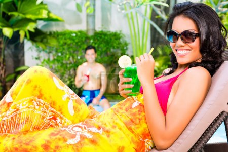 Woman at pool with cocktail