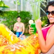 Asian woman tanning at pool on sun lounger drinkin...