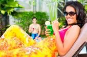 Žena v bazénu s koktejlem