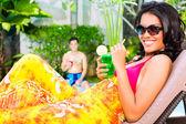 Frau am Pool mit cocktail