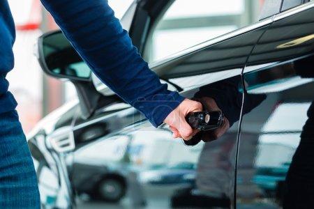 Photo pour Jeune homme à côté d'une nouvelle voiture dans le concessionnaire automobile, évidemment, il achète l'automobile, ou faire un essai routier - image libre de droit