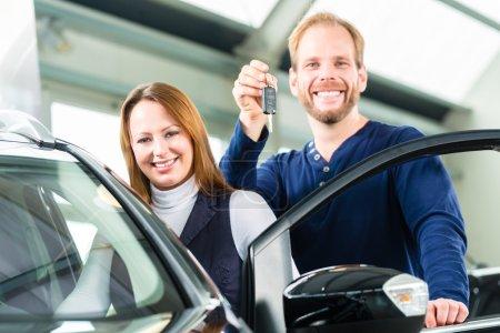Photo pour Jeune homme à côté d'une nouvelle voiture dans le concessionnaire automobile, évidemment, il achète l'automobile, ou faire un essai routier et tenant les clés en main - image libre de droit