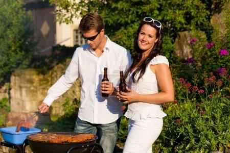 Couple doing BBQ in garden