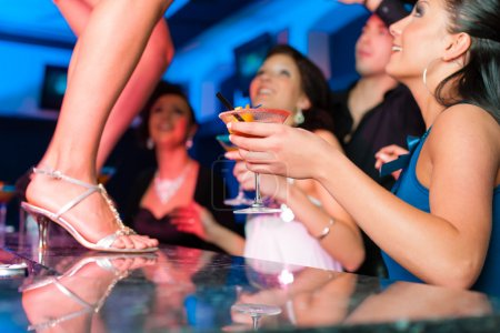 Woman in bar or club is dancing on the table