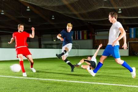 Photo for Men team playing football or soccer indoor and trying to score a goal - Royalty Free Image