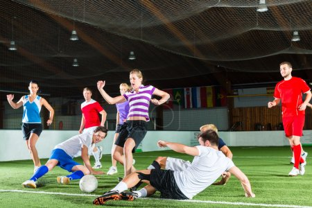 Photo for Men and women in mixed sport team playing football or soccer indoor and trying to score goal - Royalty Free Image