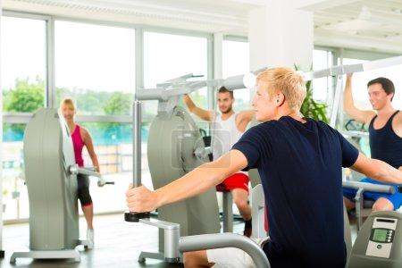 Photo pour Groupe d'hommes train machine dans un club de fitness ou de gym - image libre de droit