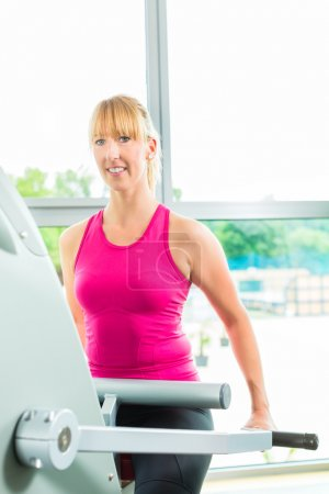 Woman in sport gym on stepper