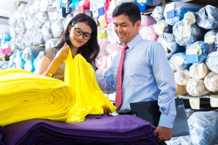 Asian colleagues in a warehouse choosing cloths